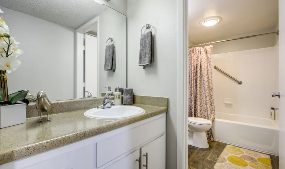 Tiled shower and granite countertop in a model home's bathroom at The Ranch at Bear Creek Apartments & Townhomes in Lakewood, Colorado