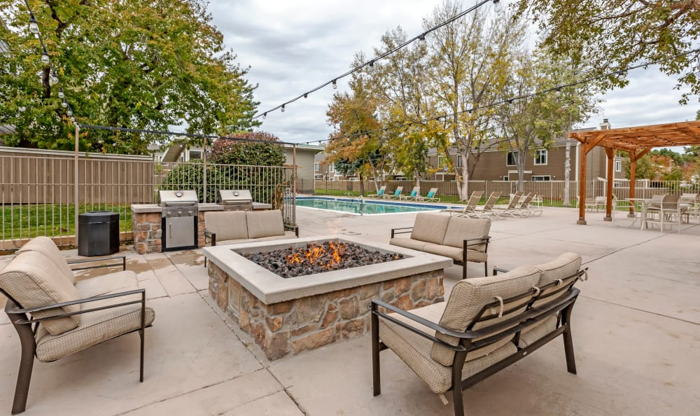 Comfortable seating in front of the fire pit at The Ranch at Bear Creek Apartments & Townhomes in Lakewood, Colorado