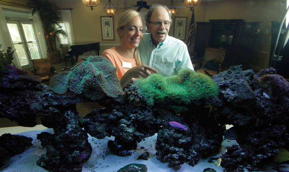 Staff member and resident looking through fish tank at Tequesta Terrace in Tequesta, Florida