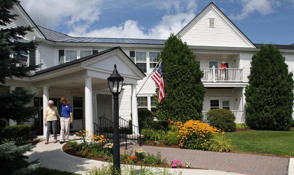 Resident and staff outside of the front entrance of Valley Terrace in White River Junction, Vermont
