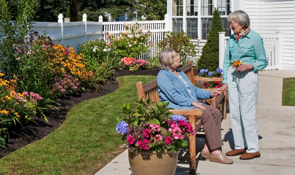 Residents enjoying the sunshine and flowers outside of Wheelock Terrace in Hanover, New Hampshire