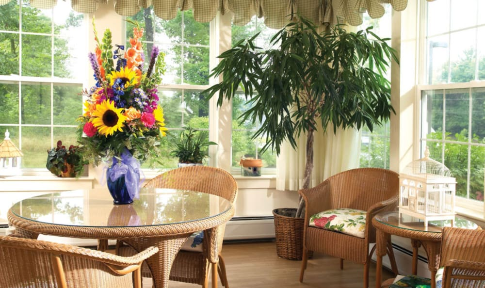 Sunlit dining room area decorated with a large bouquet of flowers at Windham Terrace in Windham, New Hampshire