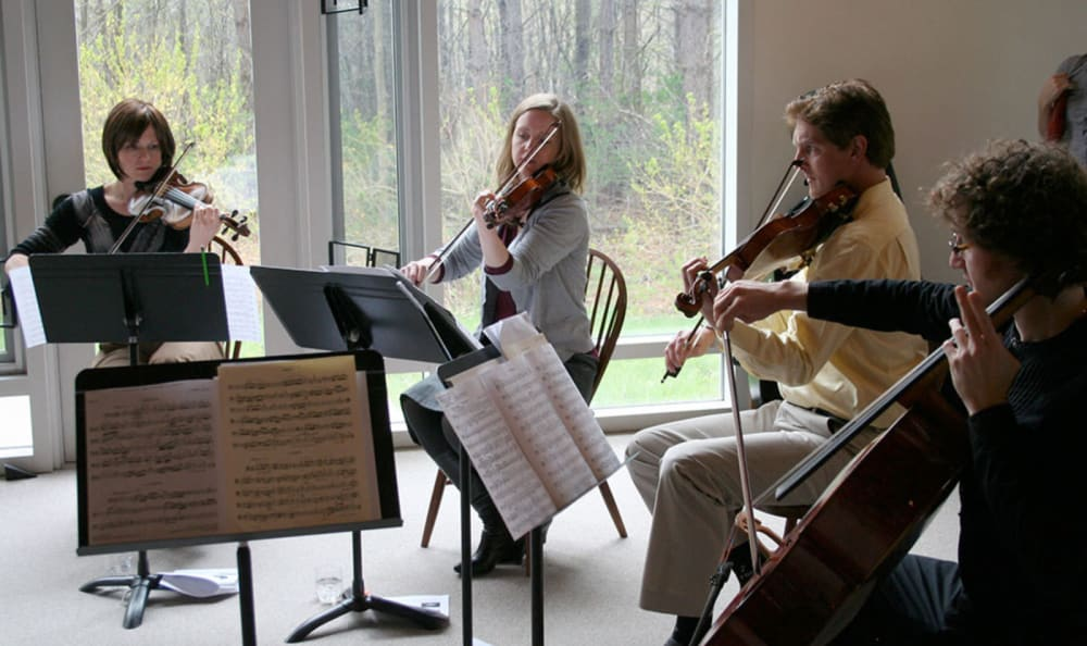Guests playing music for residents at Woodstock Terrace in Woodstock, Vermont