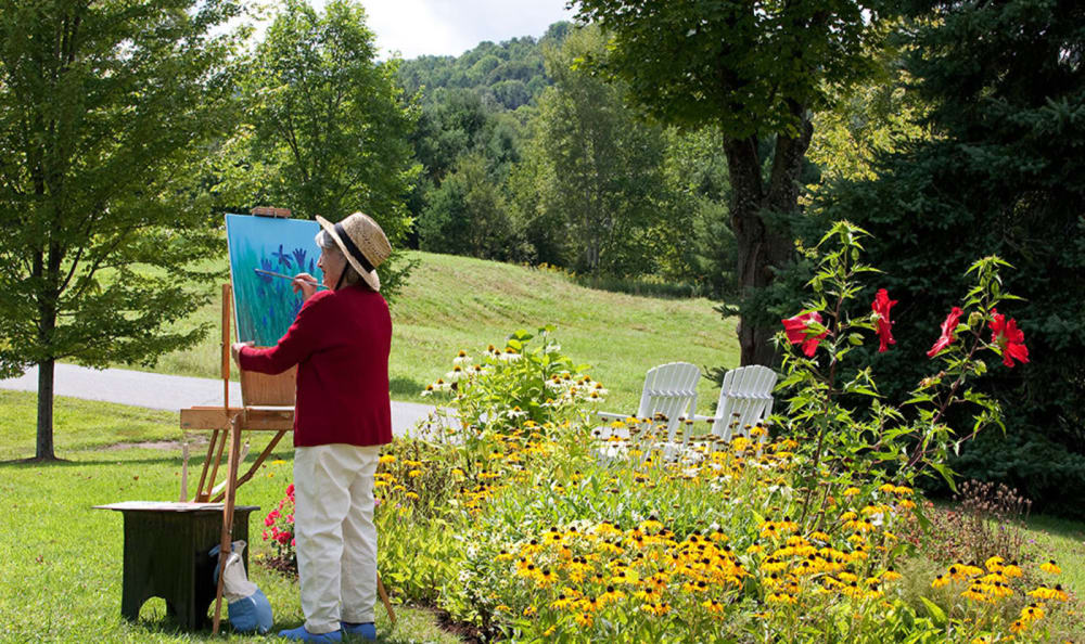 Resident painting outside at Woodstock Terrace in Woodstock, Vermont