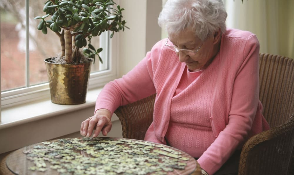 Resident putting together a puzzle at Woodstock Terrace in Woodstock, Vermont