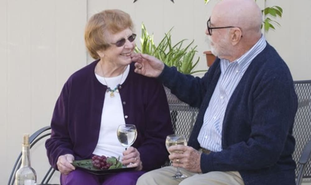 Two residents enjoying a snack and drinks outdoors at Armour Oaks Senior Living Community in Kansas City, Missouri.