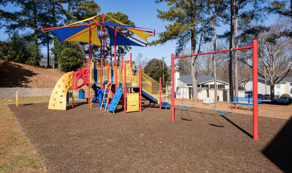 Children's playground with a swing set at Premier Apartments in Austell, Georgia