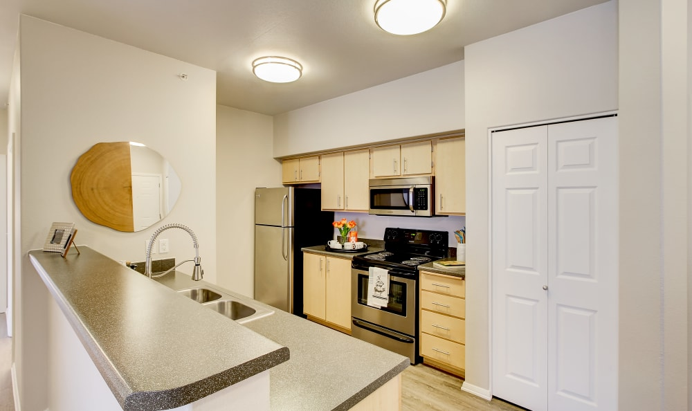 Modern kitchen with granite-style countertops and stainless-steel appliances in a model home at River Trail Apartments in Puyallup, Washington-