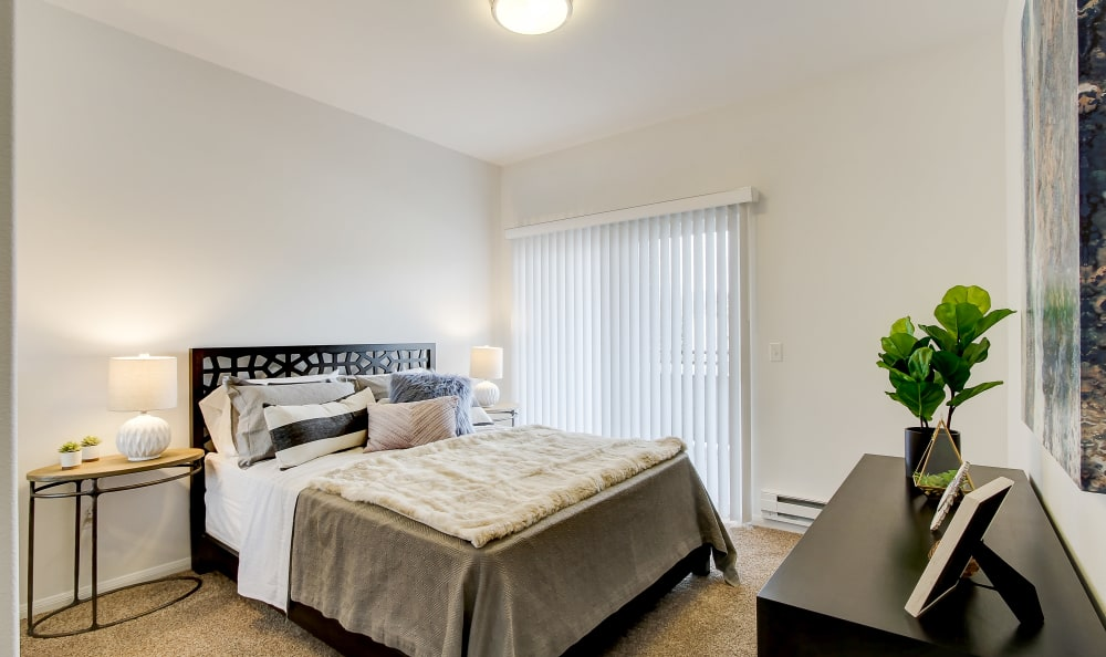 Bedroom with sliding door to a private balcony in a model home at River Trail Apartments in Puyallup, Washington