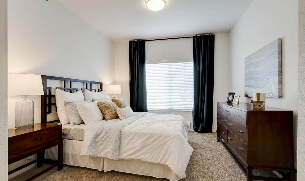 Spacious bedroom with large windows in a model home at River Trail Apartments in Puyallup, Washington