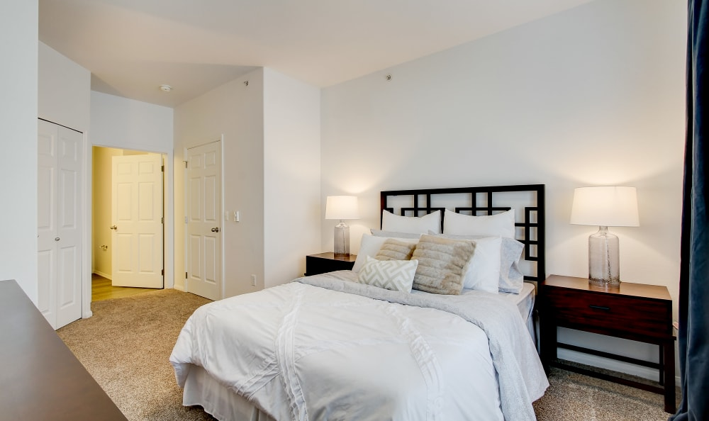 Large master bedroom with an en suite bathroom in a model home at River Trail Apartments in Puyallup, Washington