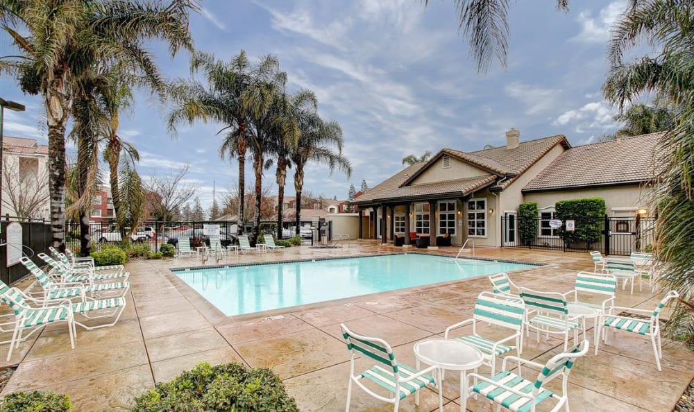 Swimming pool area with plenty of chaise lounge chairs at Eaglewood Apartments in Woodland, California