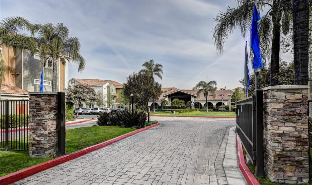 Gated entrance with cobblestone driveway at Sierra Oaks Apartments in Turlock, California