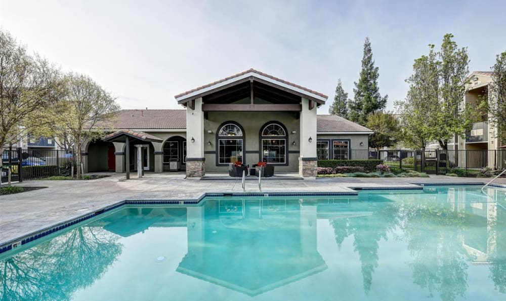 View of the resident clubhouse from across the pool at Sierra Oaks Apartments in Turlock, California
