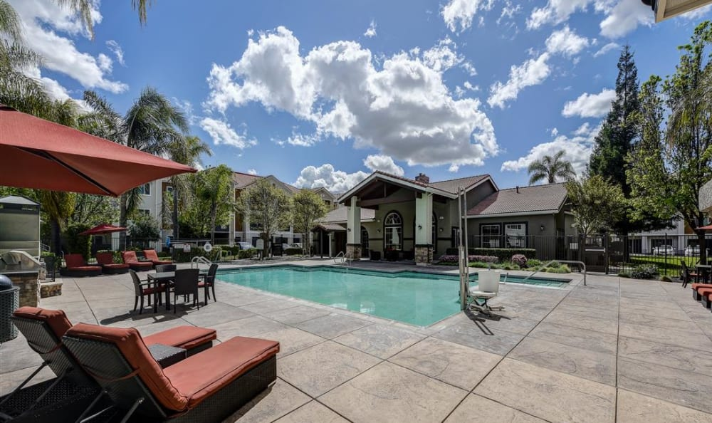Umbrellas and chaise lounge chairs near the pool on a beautiful day at Sierra Oaks Apartments in Turlock, California