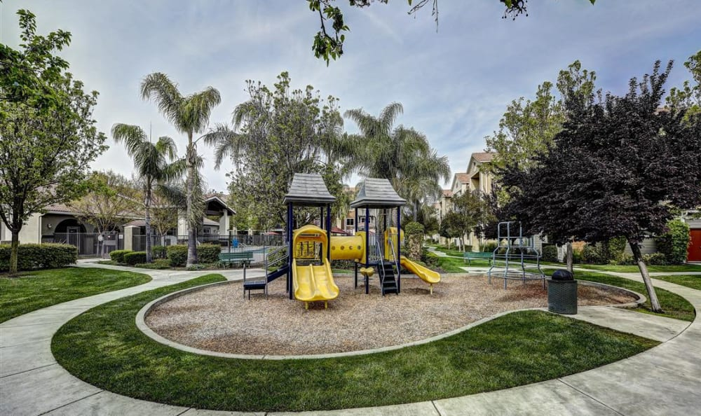 Very well-maintained landscaping surrounding the children's playground at Sierra Oaks Apartments in Turlock, California