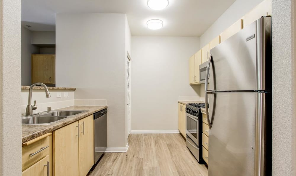 Beautifully renovated kitchen with granite countertops in a model home at Sierra Oaks Apartments in Turlock, California