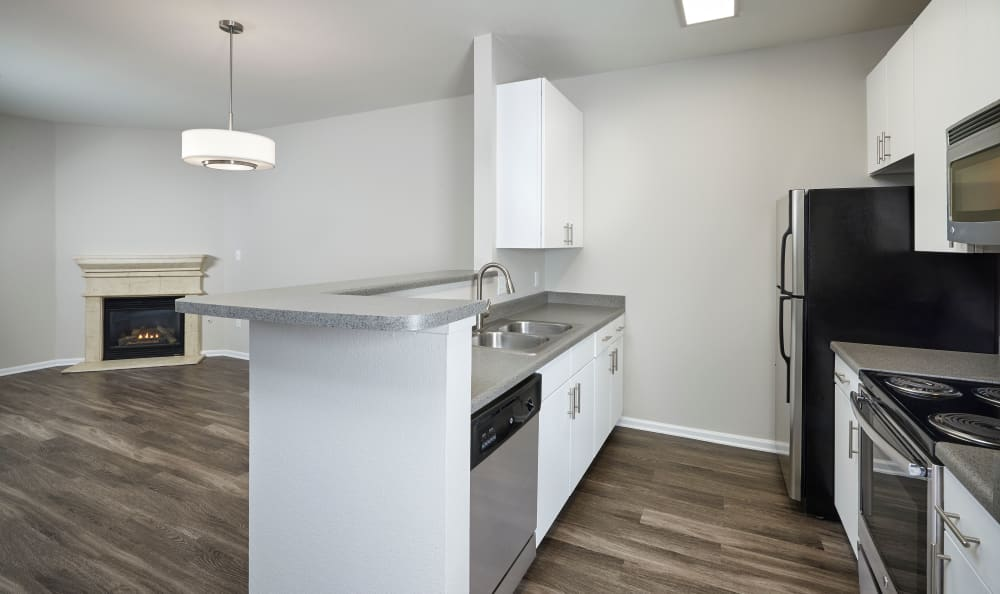 Renovated White kitchen with hard wood floor and fireplace at Bear Valley Park in Denver, Colorado