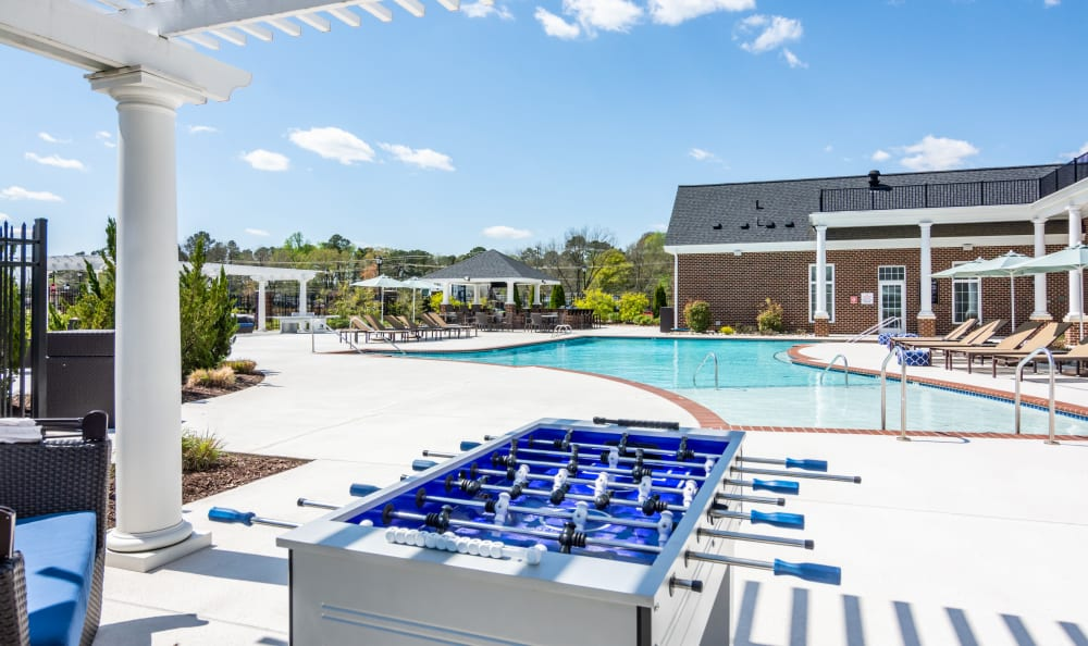 Expansive pool sundeck with outdoor games at Meridian Obici in Suffolk, Virginia
