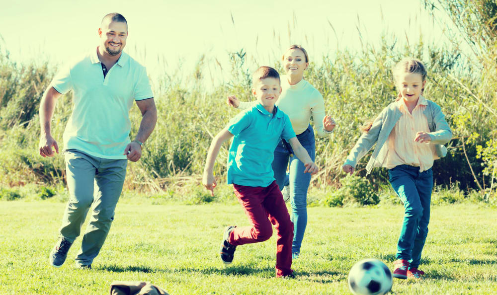 Family playing soccer at the park near Liberty Point Townhome Apartments in Draper, Utah