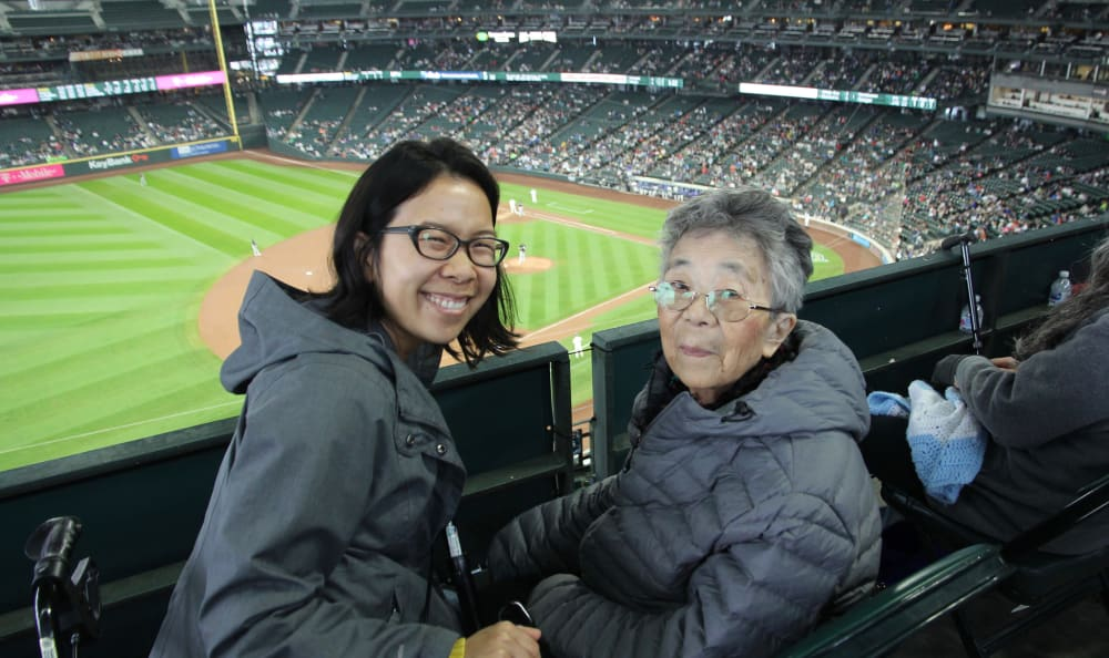 A resident and her caretaker watching at a Mariners game near Nikkei Manor in Seattle, Washington