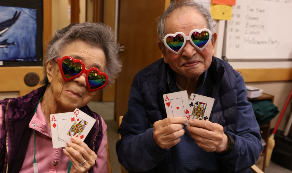 Two residents wearing heart shaped sun glasses and playing cards at Nikkei Manor in Seattle, Washington