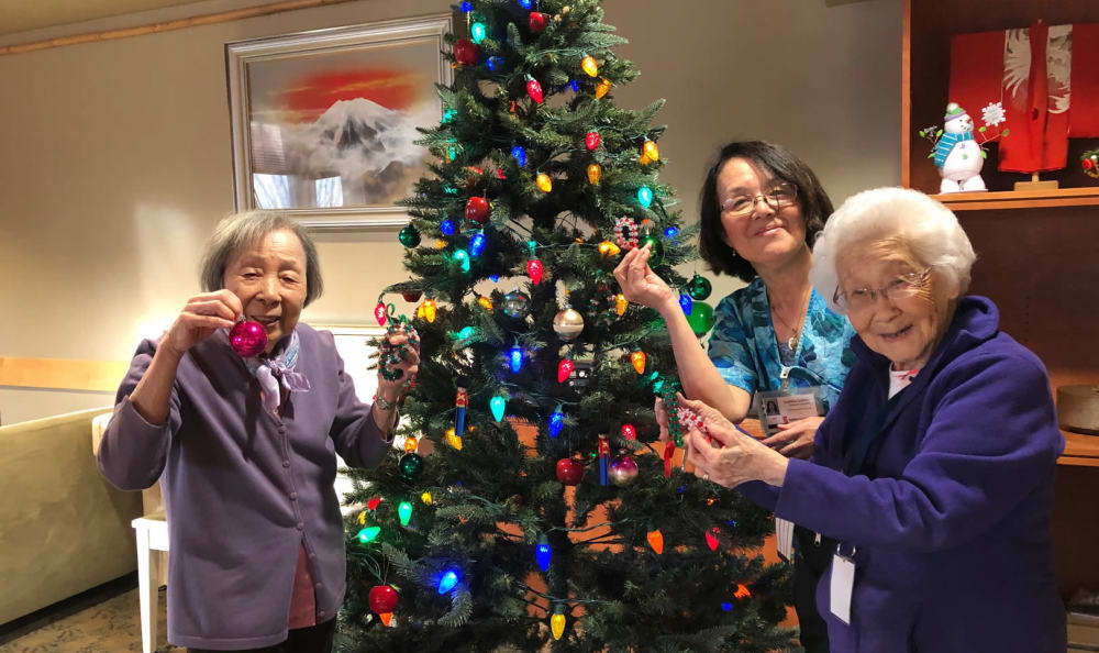 Residents putting up ornaments on a Christmas tree at Nikkei Manor in Seattle, Washington