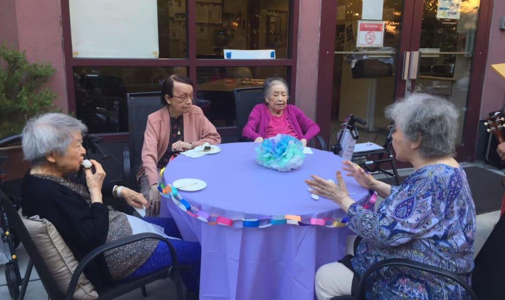 A group of residents seated around a table at Nikkei Manor in Seattle, Washington