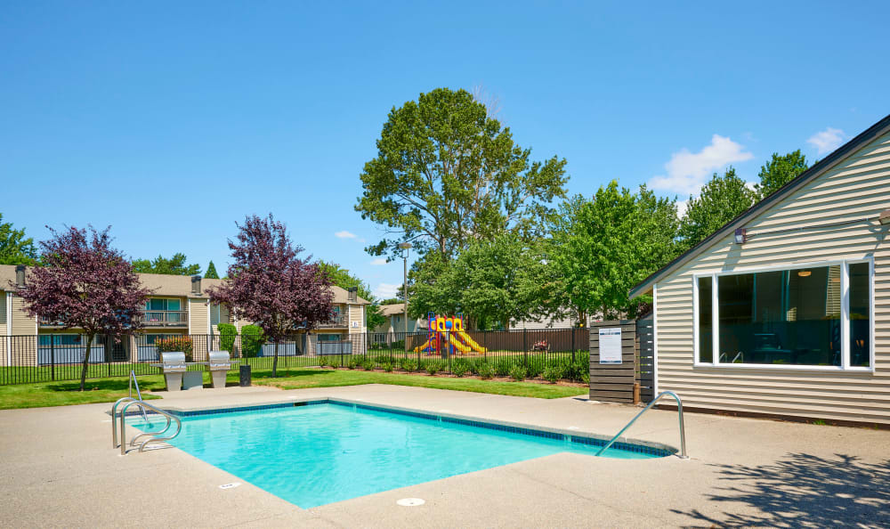 Community clubhouse and pool with mature trees in the background at Arbor Chase Apartment Homes in Kent, WA