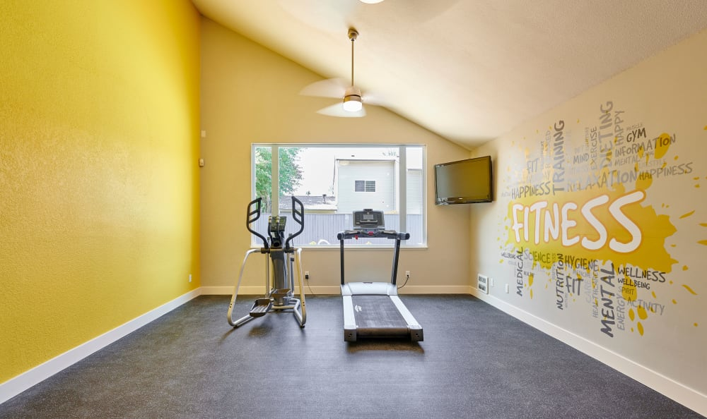 Workout equipment in brightly painted yellow room at Arbor Chase Apartment Homes in Kent, WA