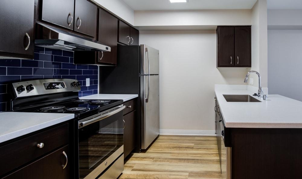 Kitchen with dark wood cabinets and black appliances at Lumen Apartments in Everett, Washington