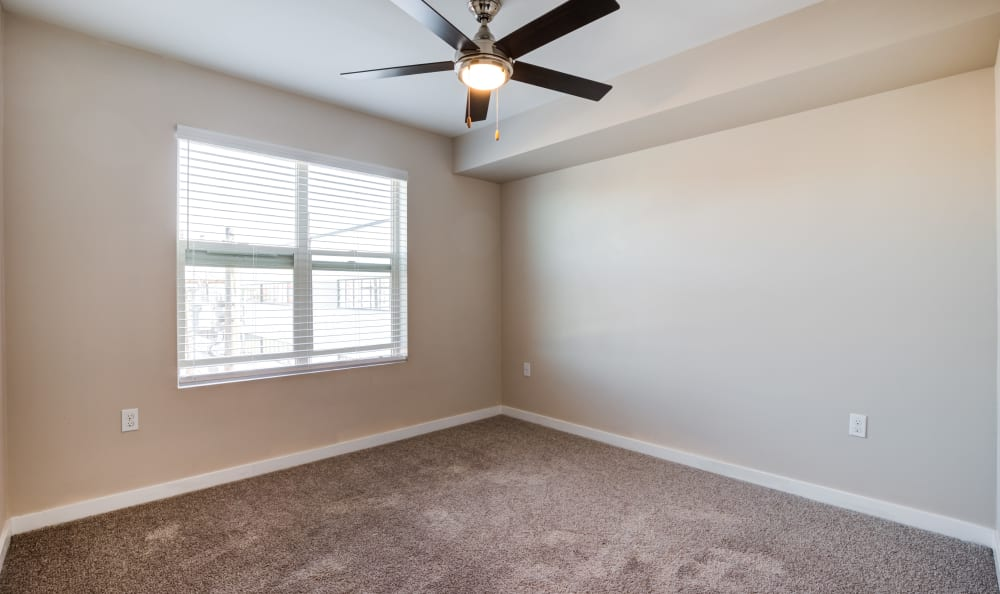 Well lit model bedroom with ceiling fan at Lumen Apartments in Everett, Washington