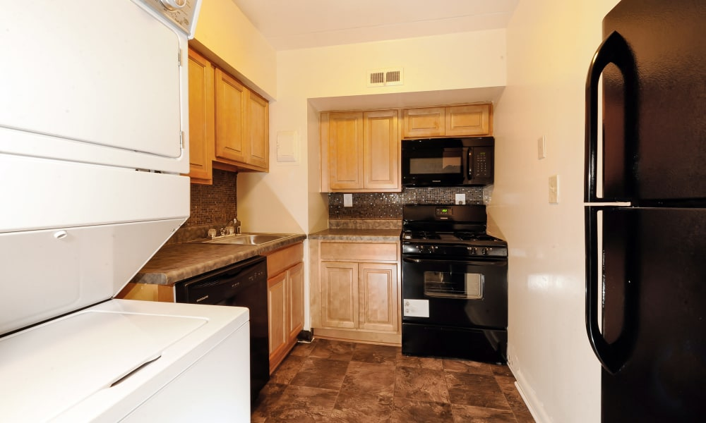 In unit washer and dryer and black fridge in a kitchen at The Reserve at Greenspring in Baltimore, MD