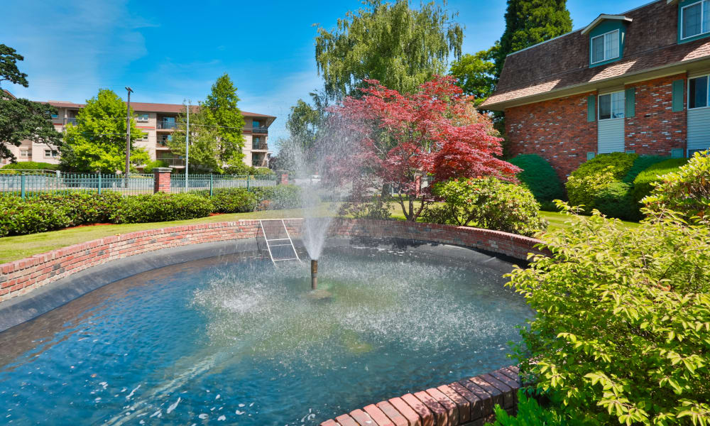 Landscaped grounds with fountain at Fraser Tolmie Apartments in Victoria, BC