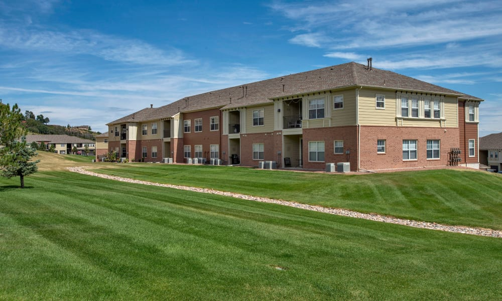 Apartment buildings and lawn at Retreat at Cheyenne Mountain Apartments