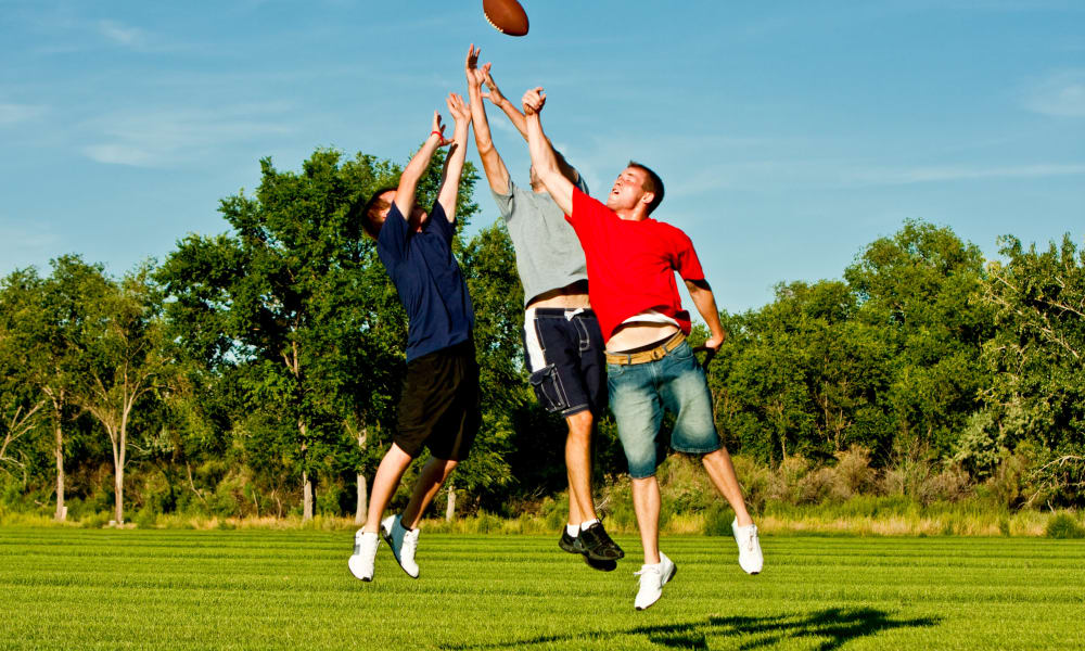 Friends having a football match near Walden Court Townhomes & Apartments in Norman, Oklahoma