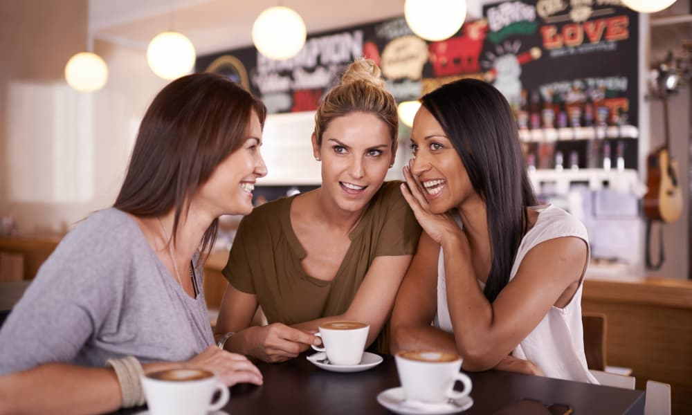 Three friends having fun at a coffee shop near Walden Court Townhomes & Apartments