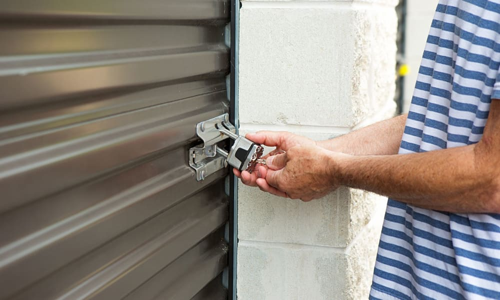 Man putting a padlock to his self storage unit at Armadillo Self Storage South in High Point, NC