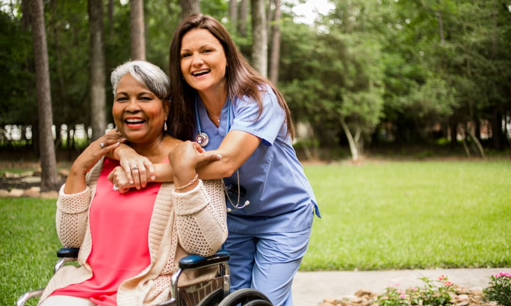 A resident out for a stroll with a nurse at Willow Brooke in Union, Missouri