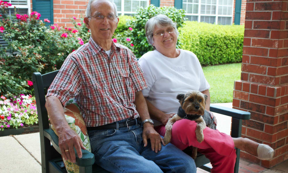 A couple at Azalea Estates of Monroe with their small dog in Monroe, LA