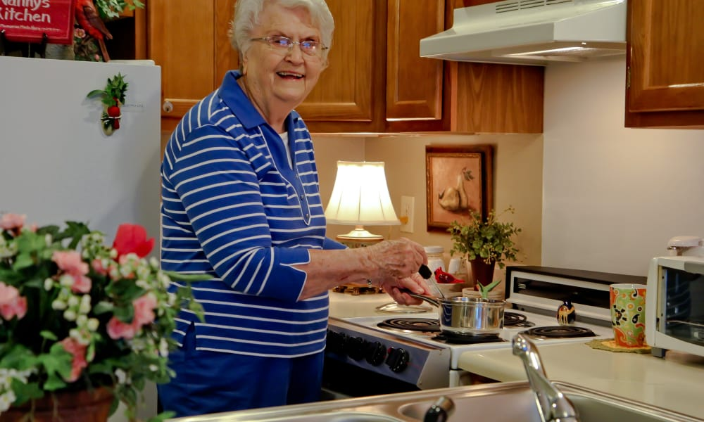 An independent resident cooking herself a meal at Azalea Estates of Monroe in Monroe, LA