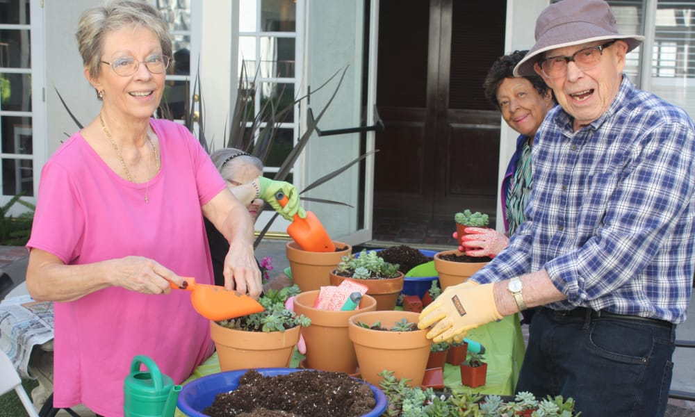 Seniors potting plants outside at Regency Park Oak Knoll in Pasadena, California