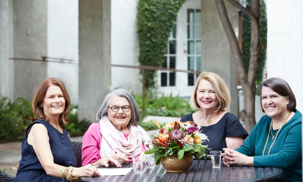 Senior lady and daughters sitting on patio at Regency Park Oak Knoll in Pasadena, California