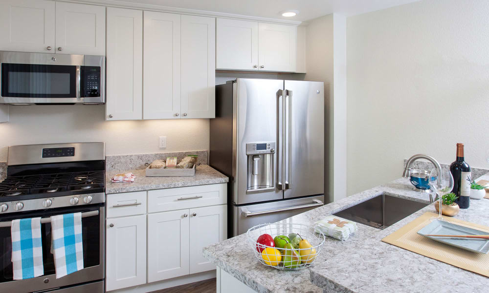 Gourmet kitchen with white cabinetry, stainless-steel appliances, and granite countertops in model home at The Arlington in Burlingame, CA