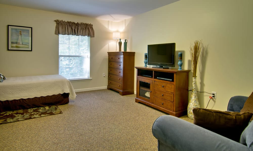 View of the bed and couch in a studio apartment at Chestnut Glen Senior Living in Saint Peters, Missouri