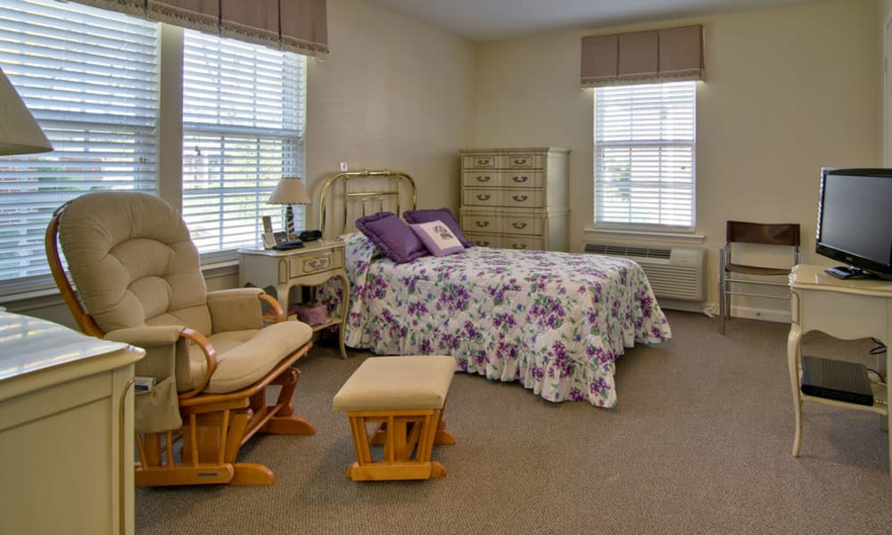 Studio apartment with a bed and seating area at Chestnut Glen Senior Living in Saint Peters, Missouri