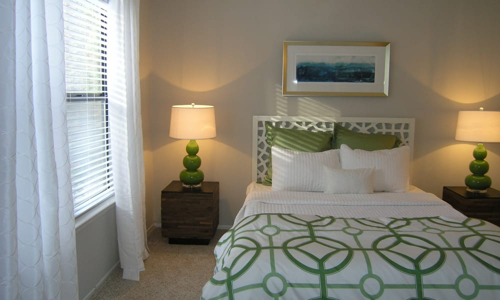 Comfortable bedroom with natural light at The Pointe at Preston Ridge in Alpharetta, Georgia