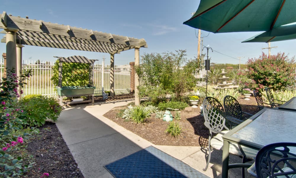 Outdoor seating and a paved walkway through the garden at Ravenwood Senior Living in Springfield, Missouri