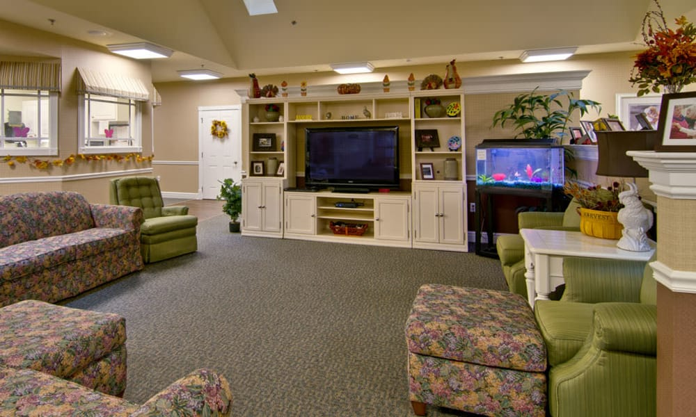 Entertainment room with comfortable seating and a fish tank at Schilling Gardens Senior Living in Collierville, Tennessee