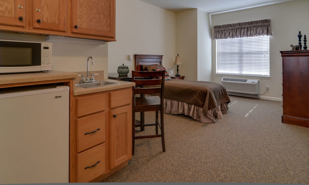 View of the kitchen and bedroom of an Assisted Living apartment at Colony Pointe Senior Living in Columbia, Missouri